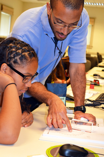 In a 2013 GLEE GAMES camp, Lynford Goddard gives a camper some one-on-one instruction during a session on optics.